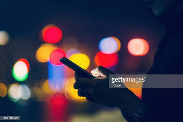 Woman using mobile phone against illuminated city lights at night
