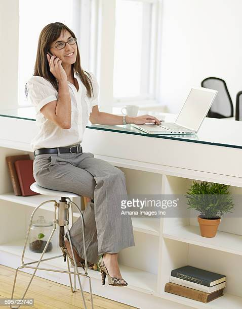 Woman Using Mobile Phone and Laptop in Office
