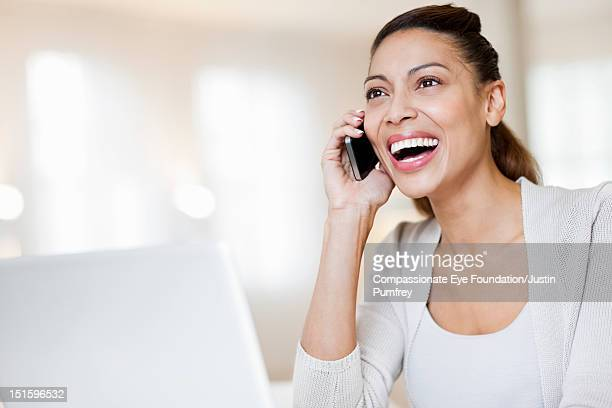 """woman using mobile phone and laptop, smiling - """"compassionate eye"""" stockfoto's en -beelden"""