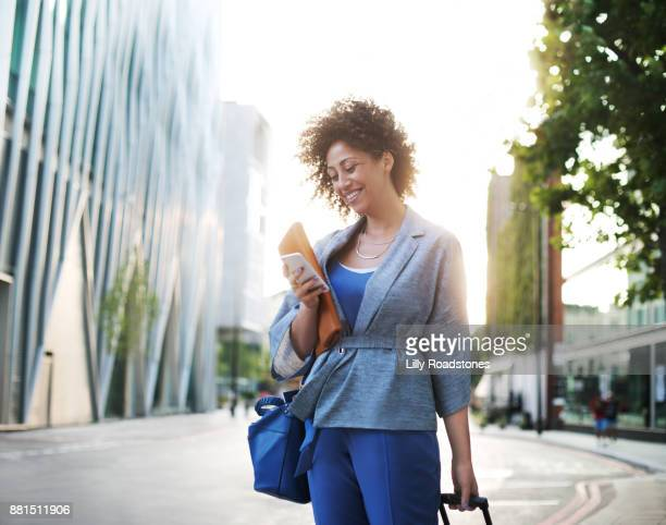 Woman using mobile phone and pulling small suitcase