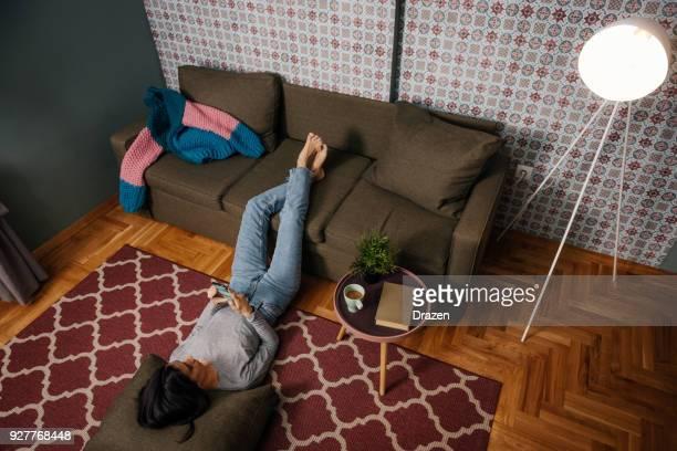 Frau mit Handy-app zur Steuerung von Temperatur zu Hause