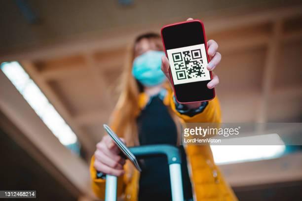 mujer usando aplicación de teléfono móvil con resultados de prueba covid-19 - pase fotografías e imágenes de stock