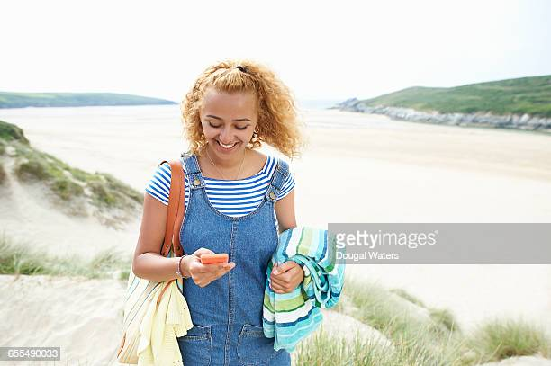 Woman using mobile phone at beach.