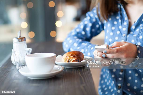 Woman using mobile phone at cafe counter