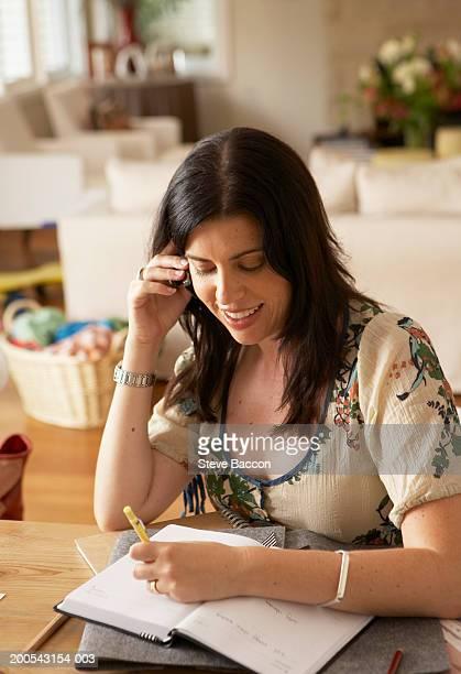 woman using mobile phone at desk at home smiling - portable information device imagens e fotografias de stock