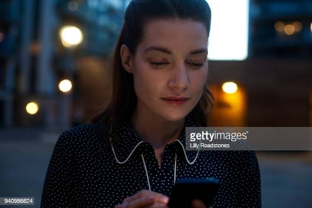 Woman using mobile phone at night (close up)