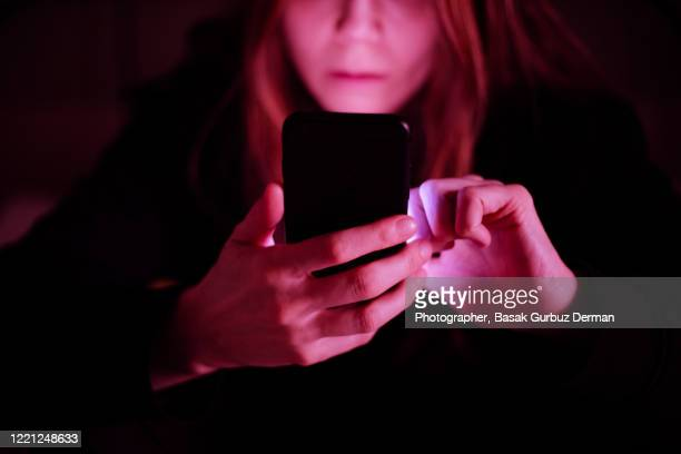 a woman using mobile phone at night, under colorful led lights at a pub / bar - negative emotion stock pictures, royalty-free photos & images