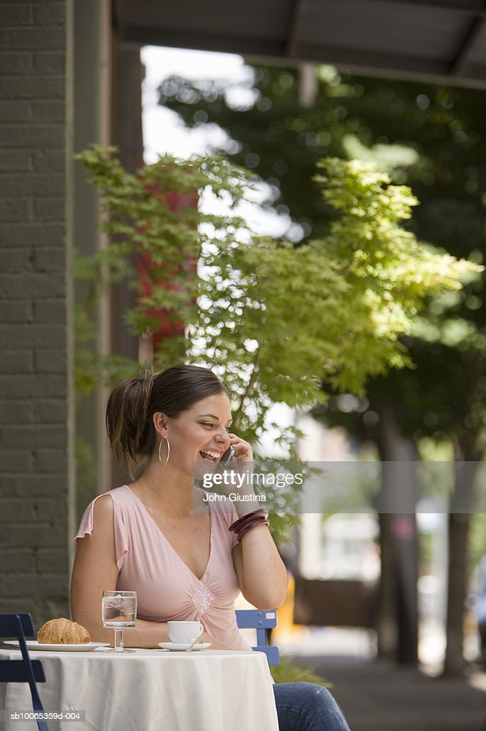 Woman using mobile phone at outdoor cafe : Foto stock