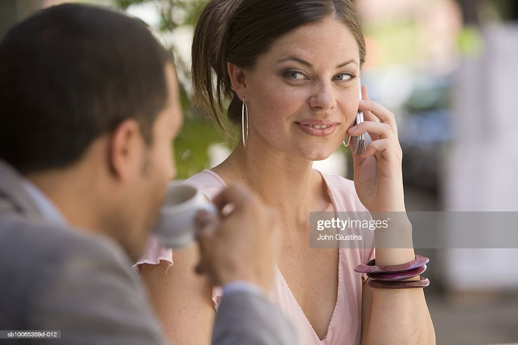 Woman using mobile phone at outdoor cafe with man drinking coffee, focus on woman : Foto stock