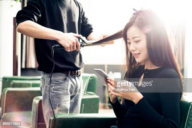 woman using mobile phone in a coiffeur studio while getting haircut. - permed hair stock photos and pictures