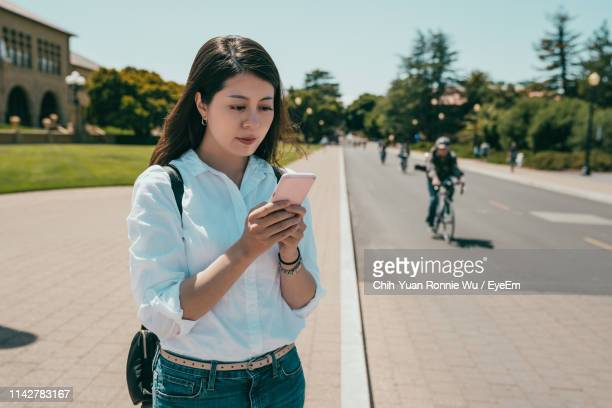 woman using mobile phone in city - palo alto and 街 ストックフォトと画像