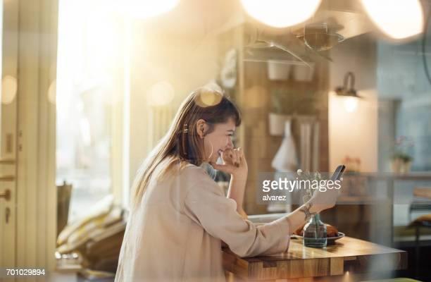 Frau mit Handy in Coffee-Shop.