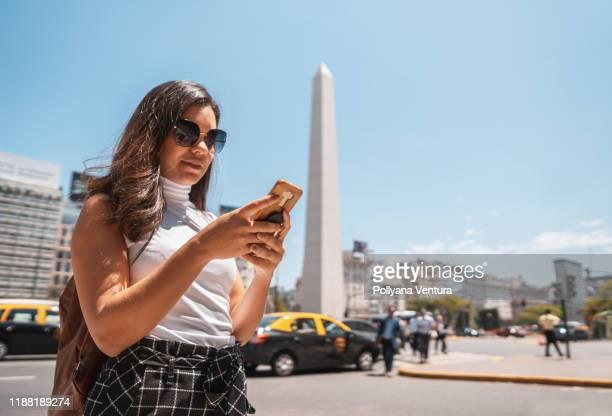 mujer que usa el teléfono móvil frente al obelisco de buenos aires - obelisco de buenos aires fotografías e imágenes de stock