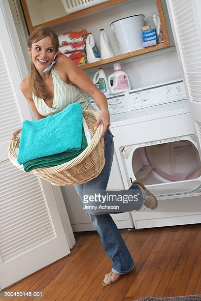 Woman using mobile phone in laundry room, closing machine with foot