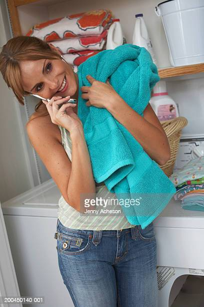 Woman using mobile phone in laundry room, smiling