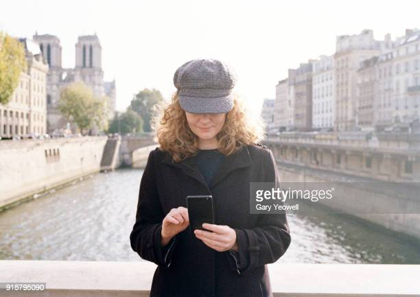 woman using mobile phone in paris - yeowell stock pictures, royalty-free photos & images
