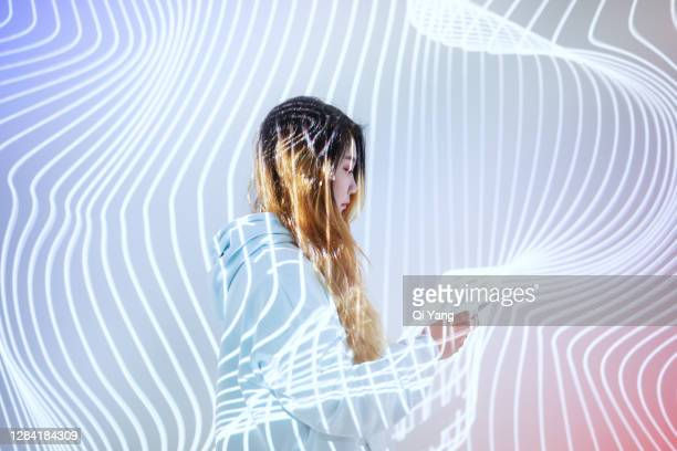 woman using mobile phone in the holographic background - blockchain stock pictures, royalty-free photos & images