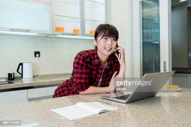女性は、台所で携帯電話を使用して - チェックシャツ ストックフォトと画像