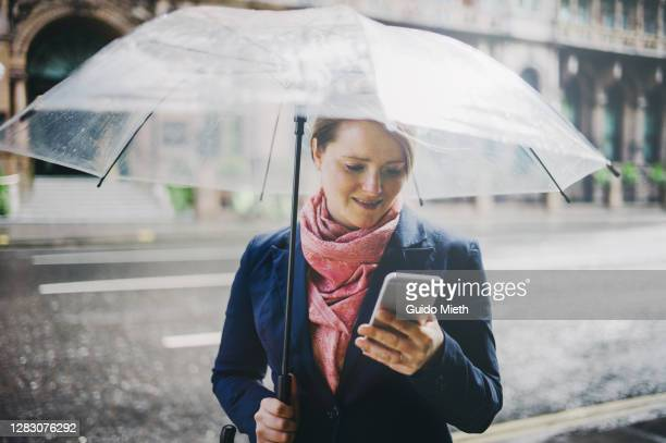 woman using mobile phone in the street while raining. - one mid adult woman only stock pictures, royalty-free photos & images