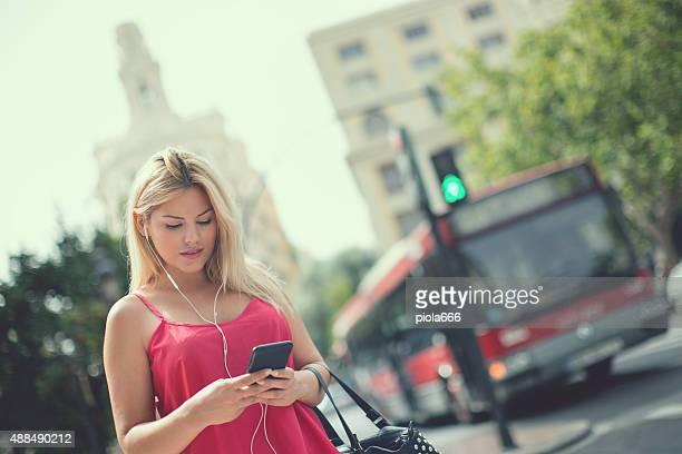Woman using mobile phone in urban settings: at traffic light