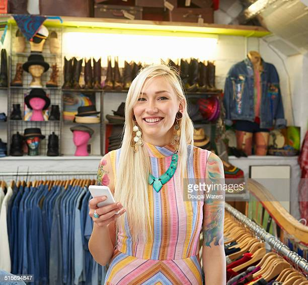woman using mobile phone in vintage clothes shop. - one young woman only stock pictures, royalty-free photos & images