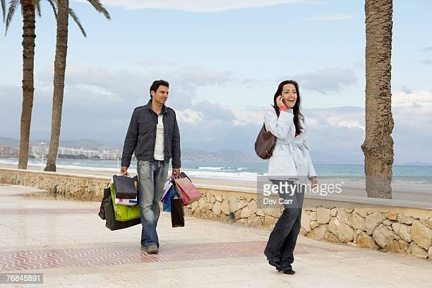 Woman using mobile phone, man carrying shopping in background
