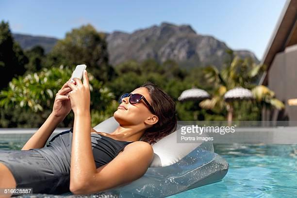 Woman using mobile phone on pool raft