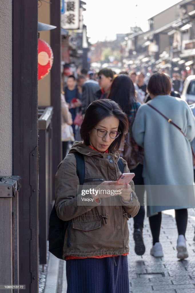 A woman using mobile phone on the street at Hanamikoji Dori, Kyoto, Japan : Stock Photo