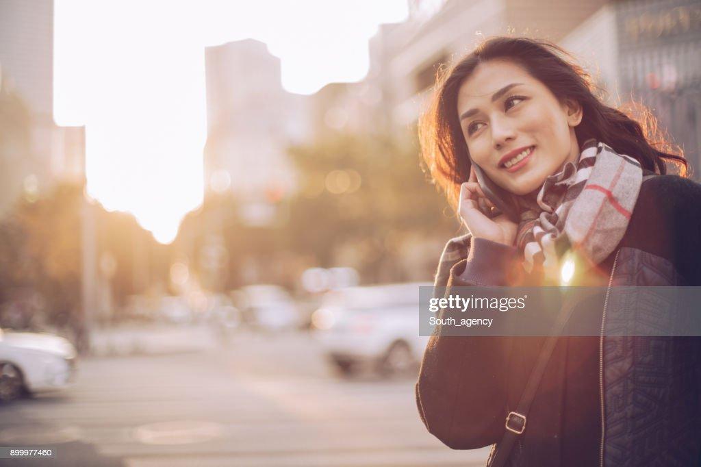 女性の携帯電話を使用して通り : ストックフォト