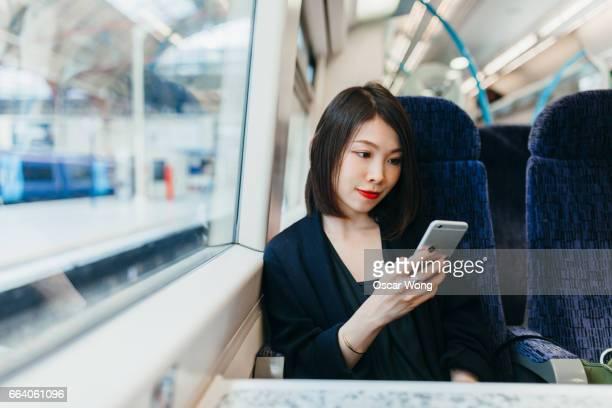 woman using mobile phone on train - bahnhof fotos stock-fotos und bilder