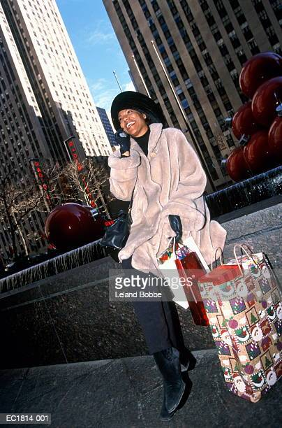 woman using mobile phone, shopping bags by side, new york city, usa - african american christmas images stock pictures, royalty-free photos & images