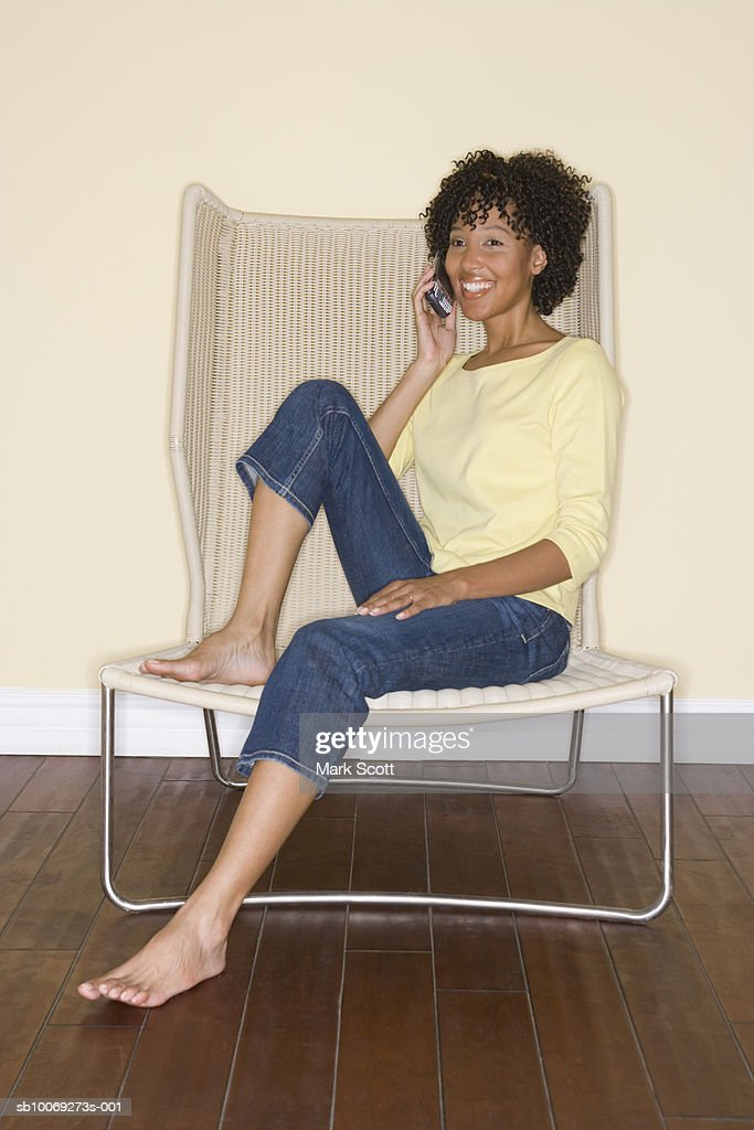 Woman using mobile phone sitting on chair, portrait : Stockfoto