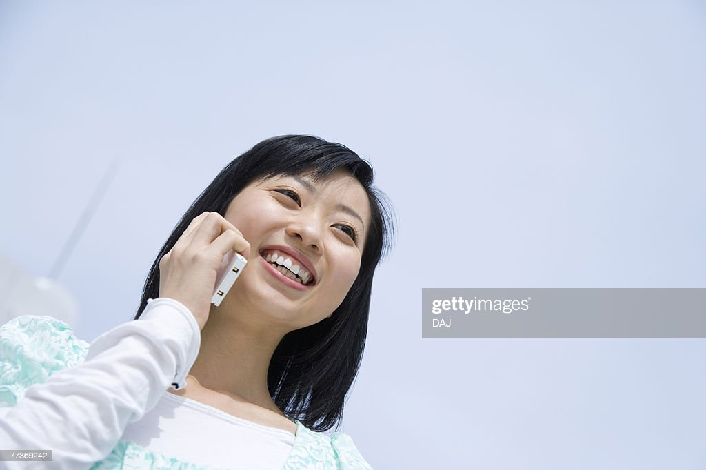 Woman using mobile phone under the blue sky, low angle view, blue background, Japan : Photo