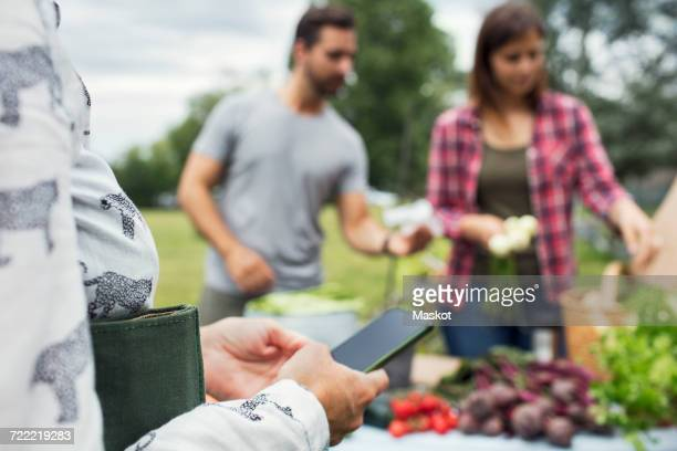 Woman using mobile phone while couple selling vegetables in background at urban garden