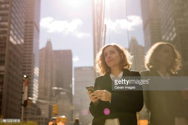 woman using mobile phone while leaning on building in city - einzelne frau über 40 stock-fotos und bilder