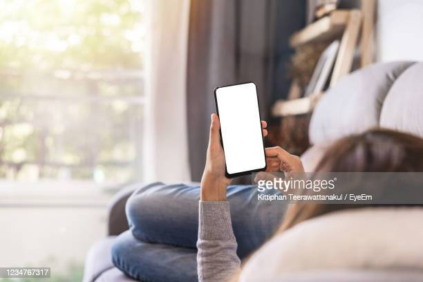woman using mobile phone while lying on sofa at home - holding stock pictures, royalty-free photos & images