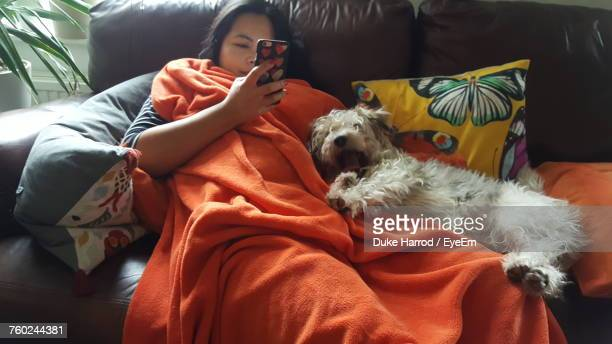 Woman Using Mobile Phone While Relaxing By Dog On Sofa At Home