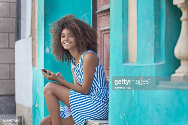 woman using mobile phone while sitting at entrance - sleeveless stock pictures, royalty-free photos & images