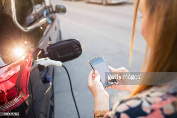 Woman using mobile phone while standing by charging electric car