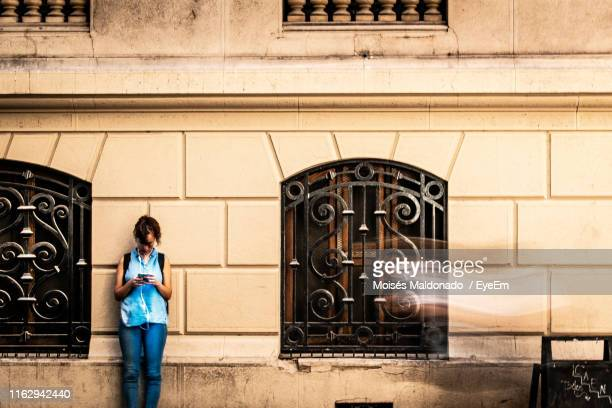woman using mobile phone white standing by built structure - santiago chile stock pictures, royalty-free photos & images