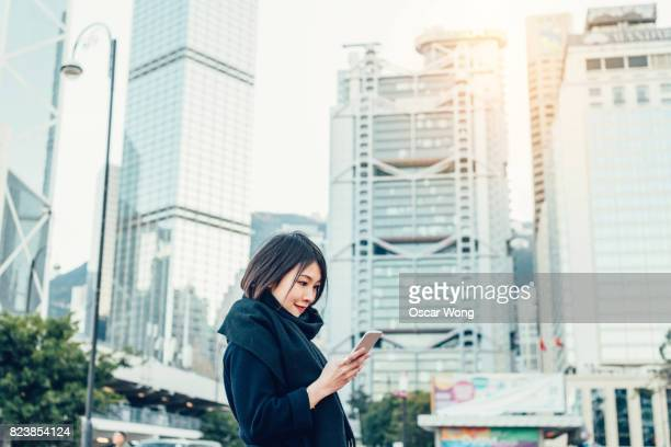 woman using mobile phone with hong kong city background - central stock pictures, royalty-free photos & images