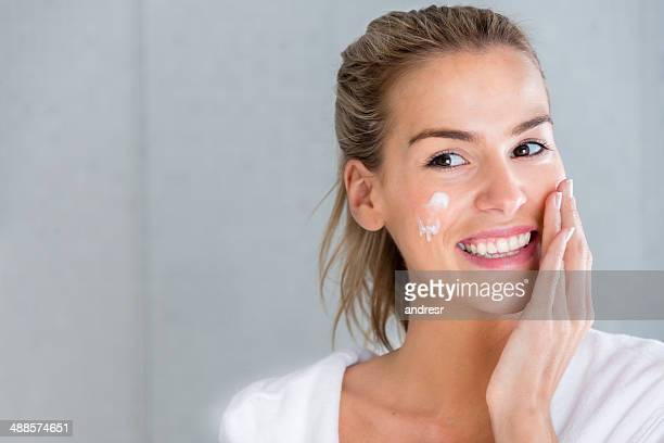 woman using moisturising cream - moisturiser stock pictures, royalty-free photos & images