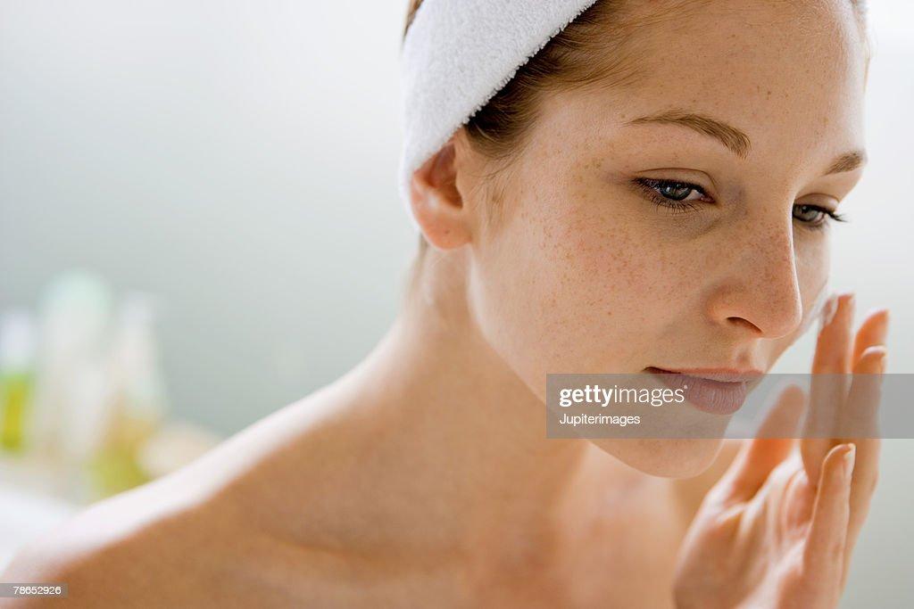 Woman using moisturizing cream : Stock Photo