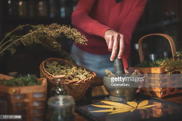 モルタルと害虫を使ってヘンプストアでマリファナの芽を挽く女性 - ストック写真 - カンナビスサティバ ストックフォトと画像
