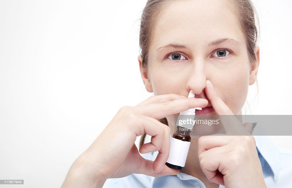 Woman using nasal spray and holding other nostril closed. : Stock Photo