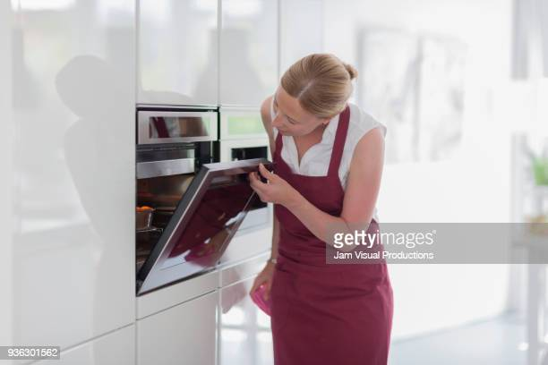 woman using oven in kitchen - oven stock pictures, royalty-free photos & images