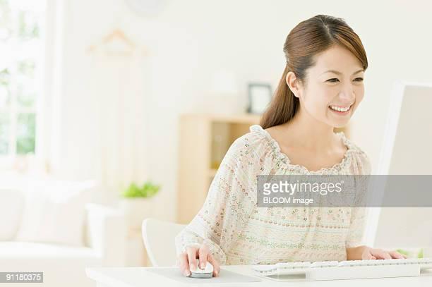 Woman using PC, smiling