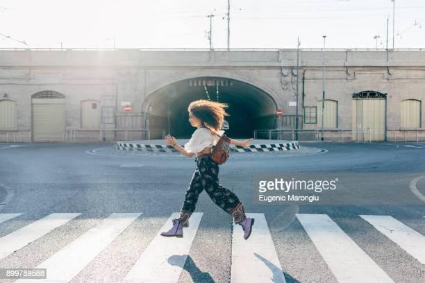 woman using pedestrian crossing, milan, italy - cruzar imagens e fotografias de stock