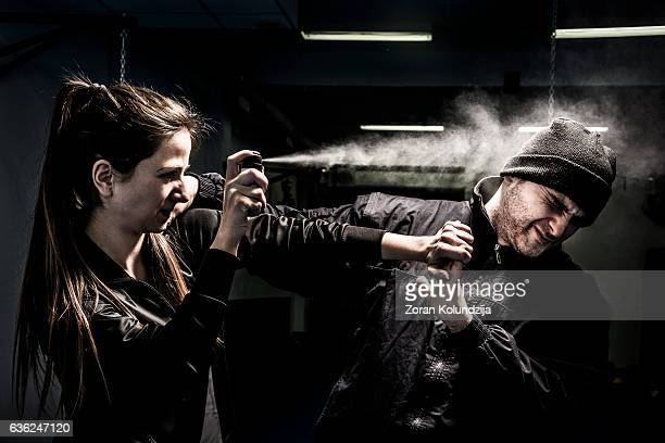 woman using pepper spray for self defense against attacker - mujer violada fotografías e imágenes de stock