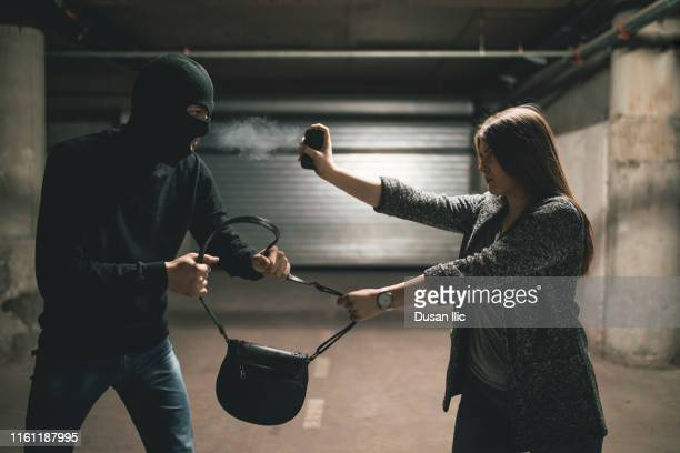 woman using pepper spray for self defense against thief - pepper spray stock pictures, royalty-free photos & images
